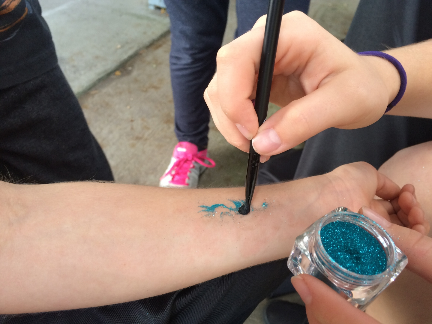 Blue Glitter Tattoo being carefully applied